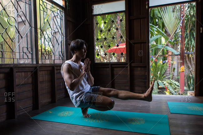 Chiang Mai, Thailand - March 5, 2017: Side view of man doing yoga in a yoga studio in Chiang Mai, Thailand