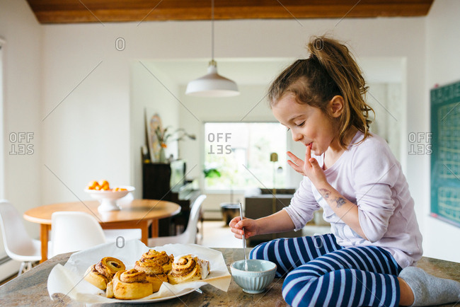 Little girl licking finger while icing cinnamon rolls