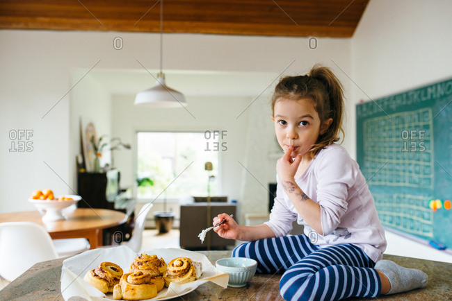 Girl licking finger while sitting on counter icing cinnamon rolls