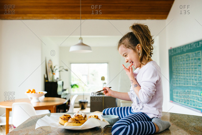 Girl licking finger while icing cinnamon rolls