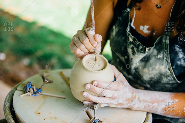 Woman writing on bottom of clay pot