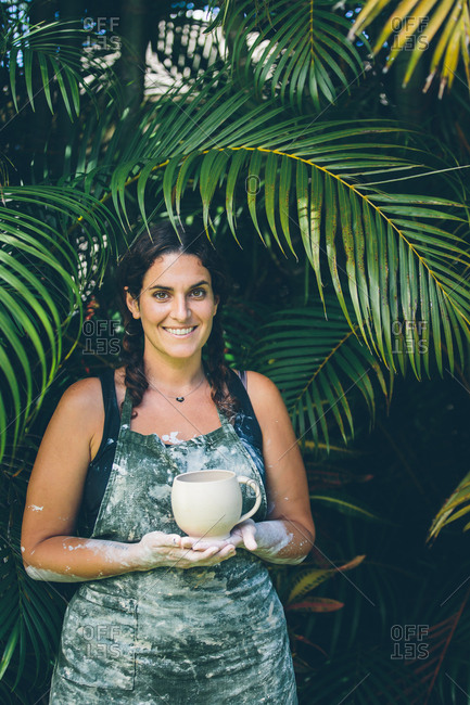 Smiling woman holding clay pot