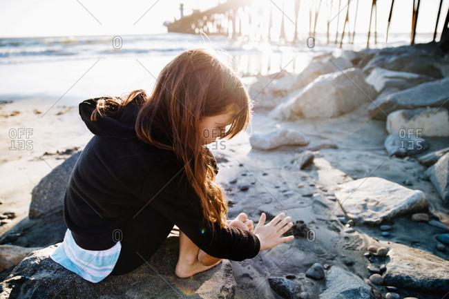 Barefoot little girl sitting on rocks by pier