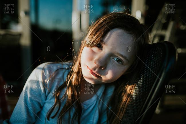 Portrait of a little girl leaning on chair in window light