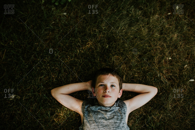 Overhead view of boy lying in the grass looking up