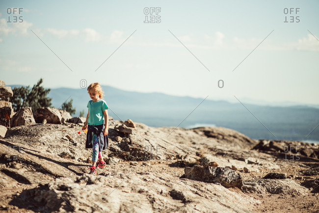 Young girl walking on rocky mountain