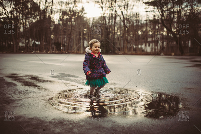 Toddler girl jumping in mud puddles
