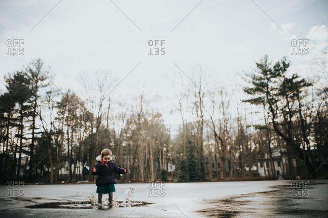 Toddler girl splashing in mud puddles