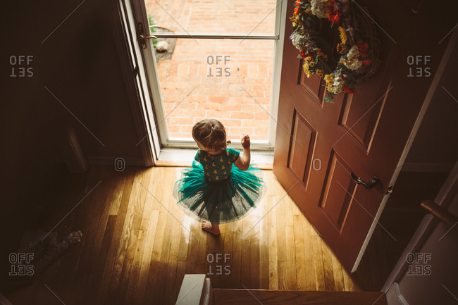 High angle view of toddler girl dancing by front door in tutu