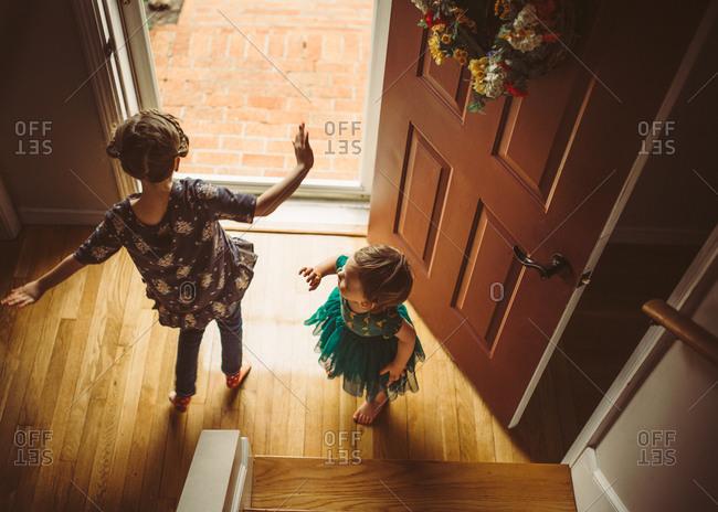 Two girls dancing by front door in tutu