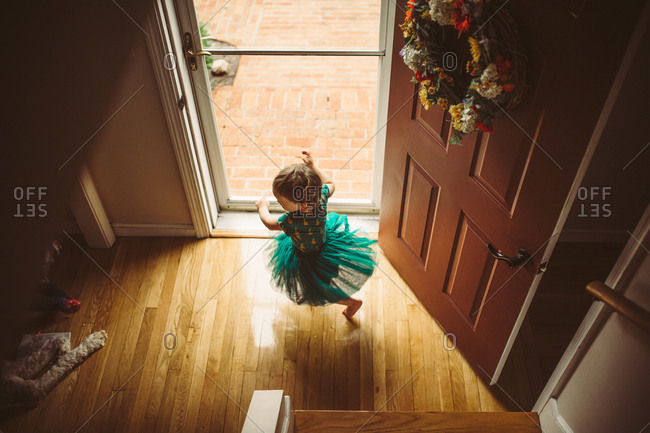 High angle view of toddler girl twirling by front door in tutu
