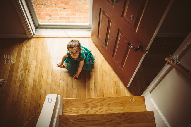 High angle view of toddler girl sitting by front door in tutu