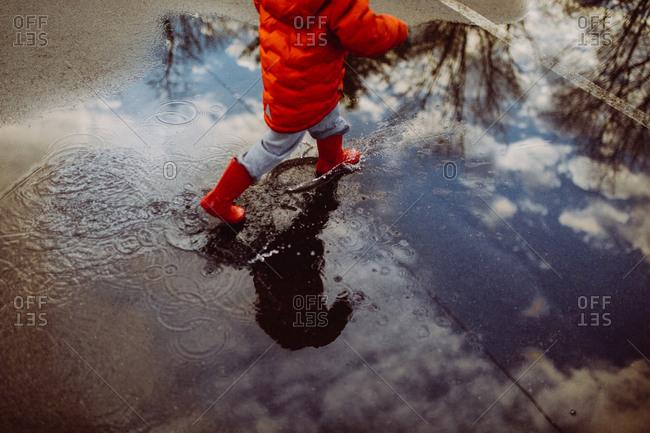 Child splashing in mud puddles