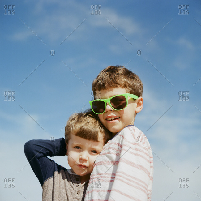 Two boys hugging outdoors
