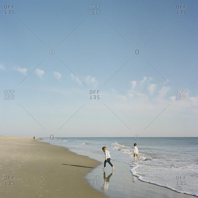 Boys walking along sea together
