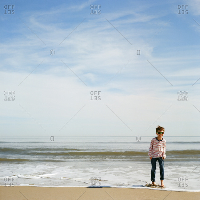 Boy smiling while standing in surf