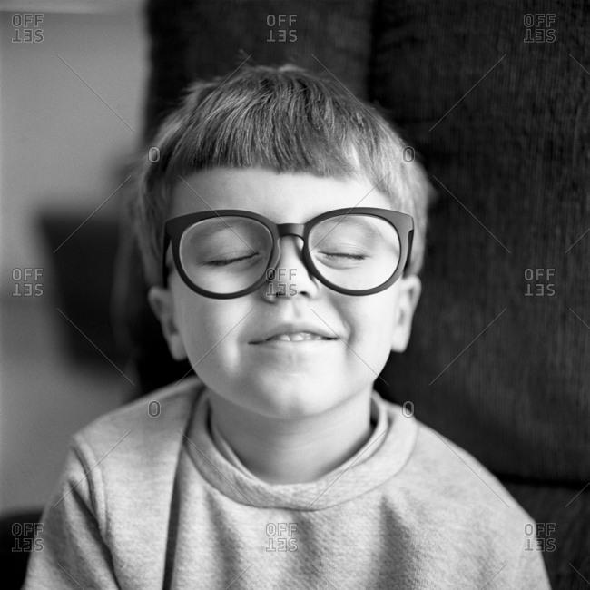 Boy smiling wearing toy glasses
