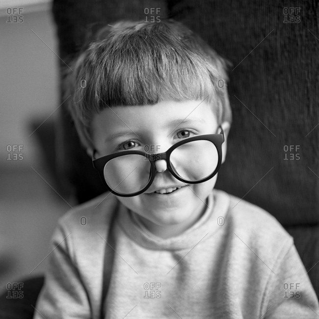 Boy looking over glasses