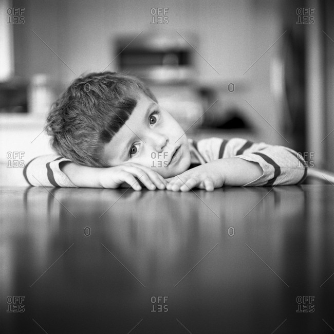 Boy resting head on a table