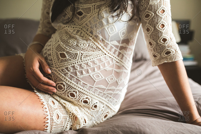 Pregnant woman in lace dress on bed