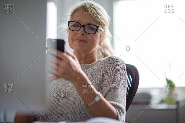 Mature businesswoman working on computer and on smartphone