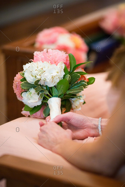Bridesmaid in a church pew holding a bouquet