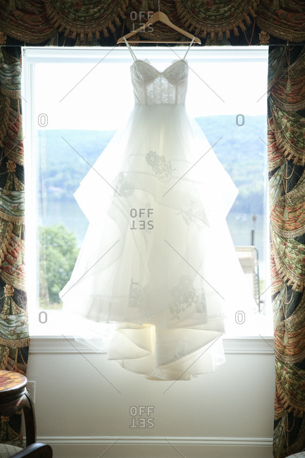Bridal gown hanging in a sunlit window with floral drapes