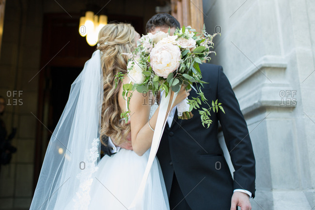 Newlywed couple kissing behind a bride's bouquet