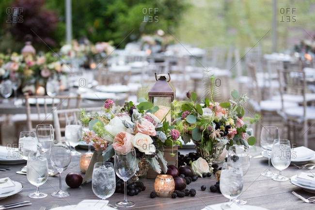 Centerpiece with flowers, fruit and a lantern at an elegant wedding ...