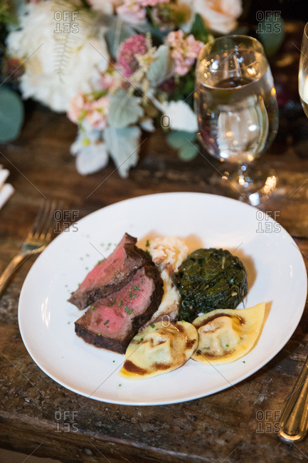 Roast beef entrees with spinach and dumplings at an elegant wedding reception