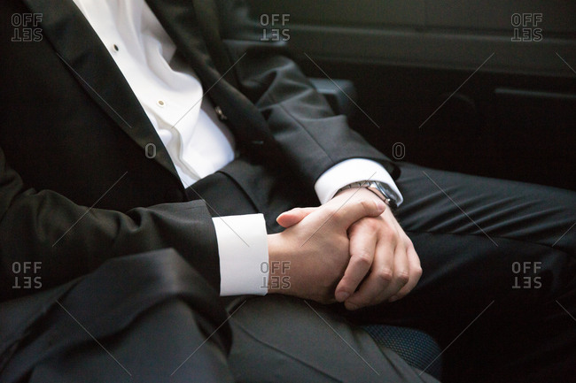 Clasped hands of a groom sitting in a car