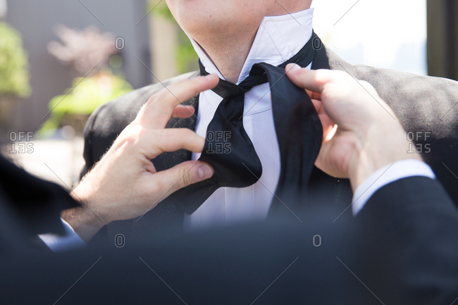 Groomsman tying a groom's bowtie on his wedding day