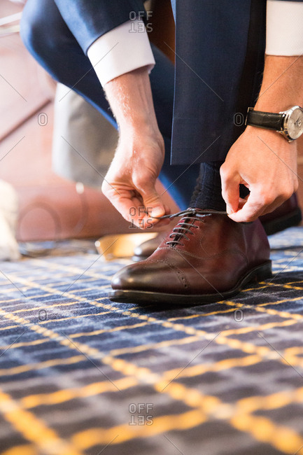 Groom kneeling to tie the laces of his shoe