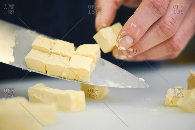 Close-up view of human hand cutting butter into cubes with big steel kitchen knife on white chopping board
