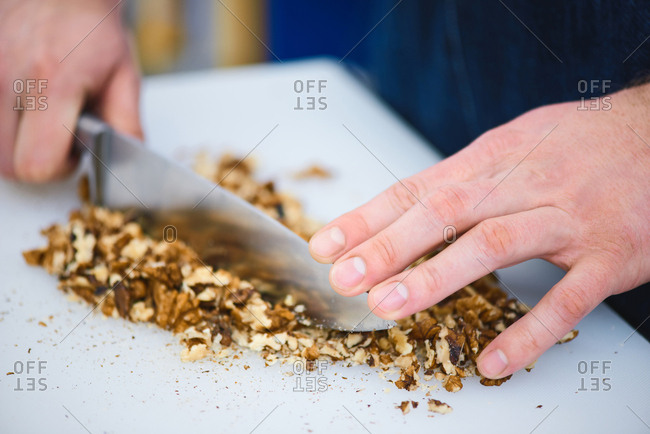 Cooking process. Close-up view of male hands chopping walnuts with steel kitchen knife on white cutting board