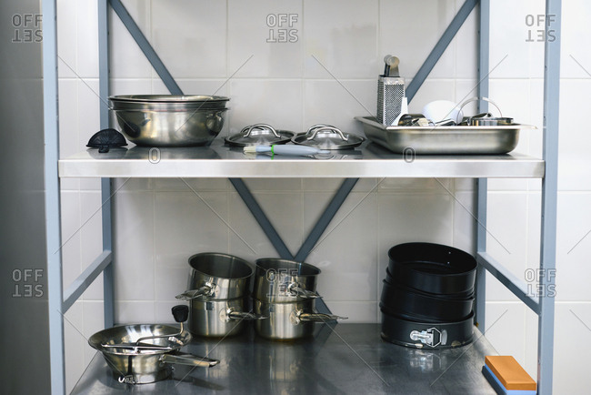 Utensil in restaurant kitchen: steel saucepans, bowls, covers and grater placed on metal shelves against white tile background