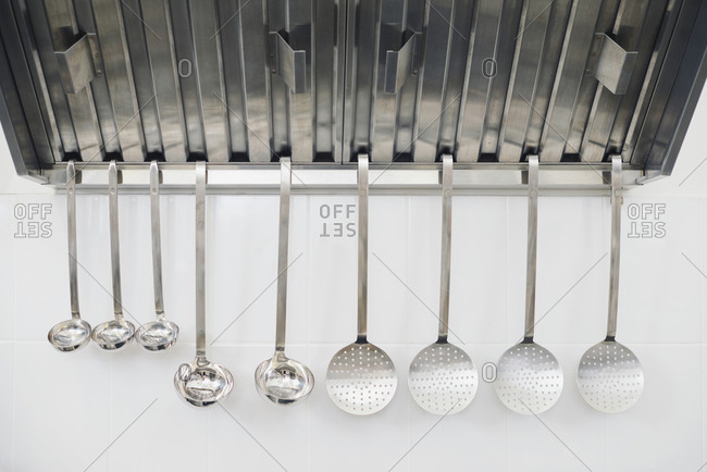 Gourmet utensil set. Ladles of different kinds and sizes hanging on white tile background in restaurant kitchen