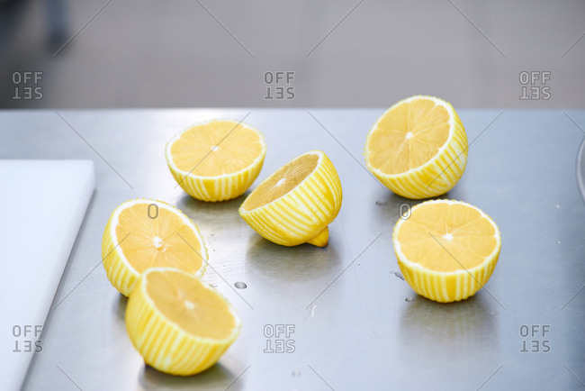 Halves of zested lemons lying on metal table next to chopping board, close-up shot