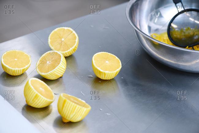 Halves of peeled ripe lemons lying on steel table beside metal bowl with lemon zest