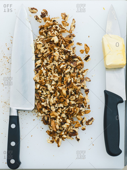 Directly above view of chopped walnuts lying on a white cutting board beside kitchen knives with a pat of butter