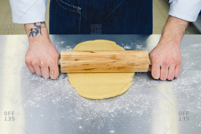 High angle view of male chef with tattoo on hand rolling cookie dough with wooden rolling-pin on metal kitchen table