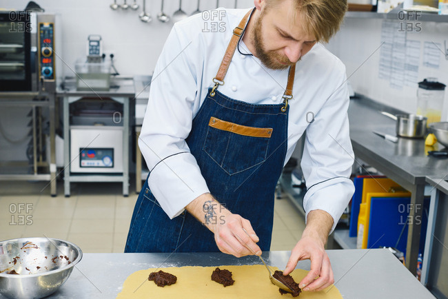 Cooking process. Professional chef with blond hair and beard putting chocolate mixture on rolled cookie dough lying on steel table in restaurant kitchen