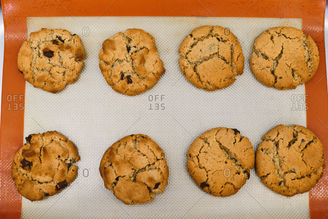 Directly above view of freshly baked crispy chocolate chip cookies lying on silicone baking mat