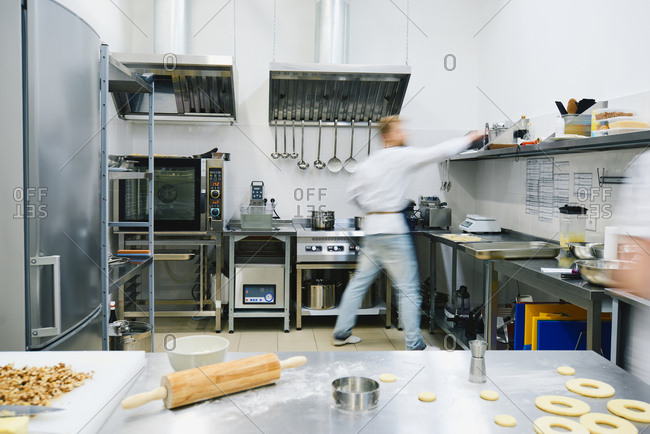 Uncooked donuts and wooden rolling-pin lying on steel table while male chef taking necessary dishes for baking, blurred motion