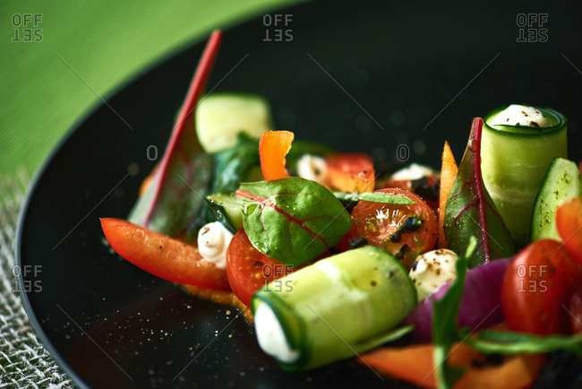 Dish from chef. Extreme close-up shot of delicious vegetable salad with cucumber and cheese rolls, cherry tomatoes, chard leaves served on black plate