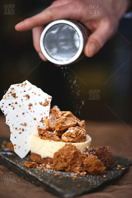 Idea for cake decoration. Close-up view of male hand sprinkling sugar powder on delicious lemon cake decorated with biscuit sponge and served on piece of stone