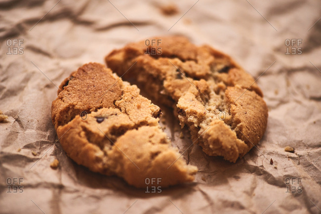 Fresh crispy oatmeal cookie broken in half lying on craft paper, extreme close-up shot