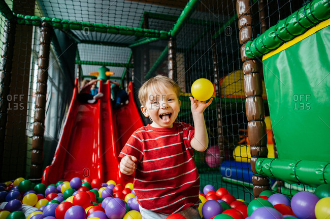 Cheeky child in a pool of colorful balls at indoor playground