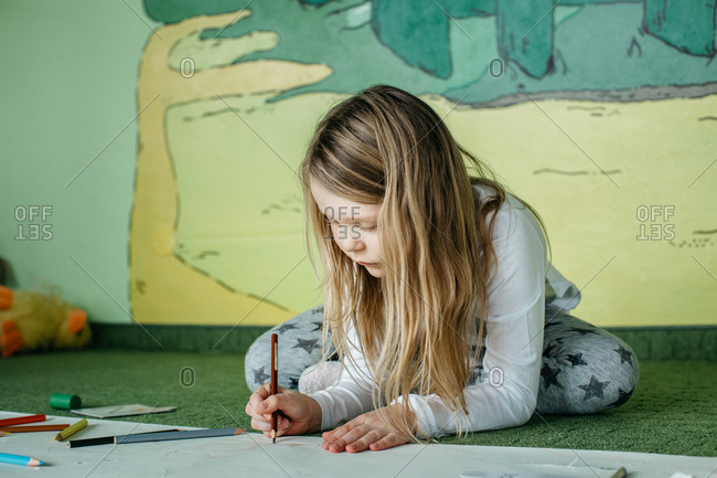 Girl sitting on the floor and drawing a picture with colored pencils