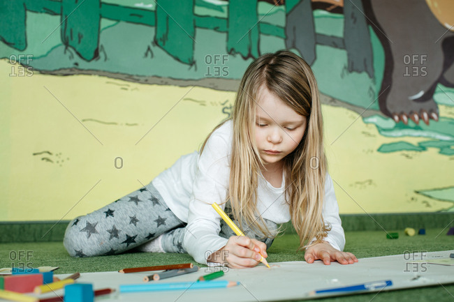 Girl lying on the floor and drawing a picture with colored pencils